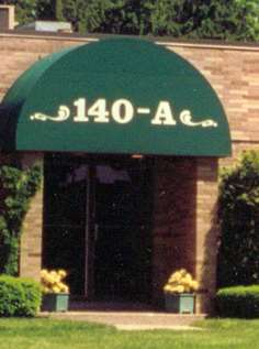 A brown brick building with a green awning with numbers and letters on it.